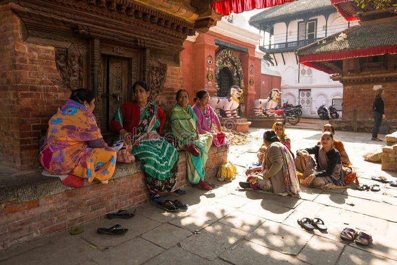 Les femmes indoues dans le sari traditionnel s'asseyent sur la vieille place de Durbar La plus grande ville du Népal image stock