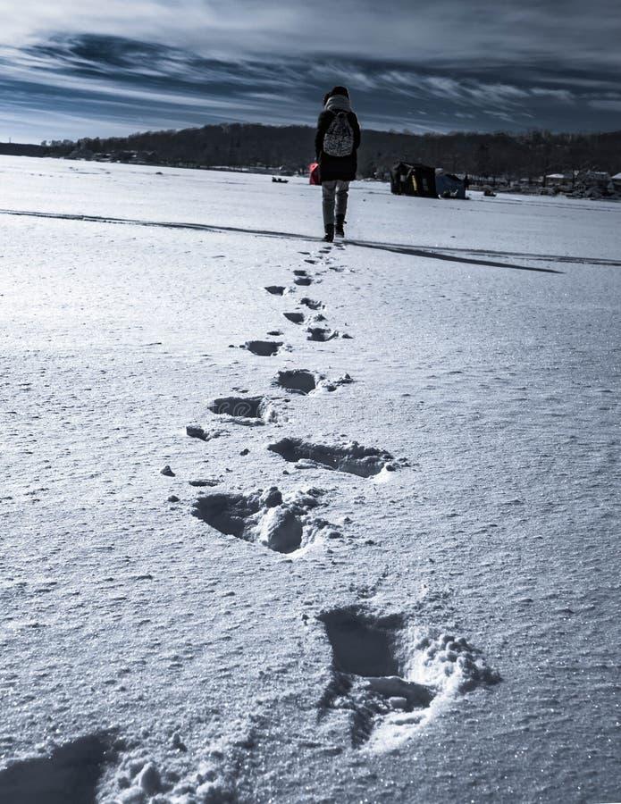 Les femmes laisse les copies profondes de pied tout en marchant sur le lac neigeux congelé photographie stock