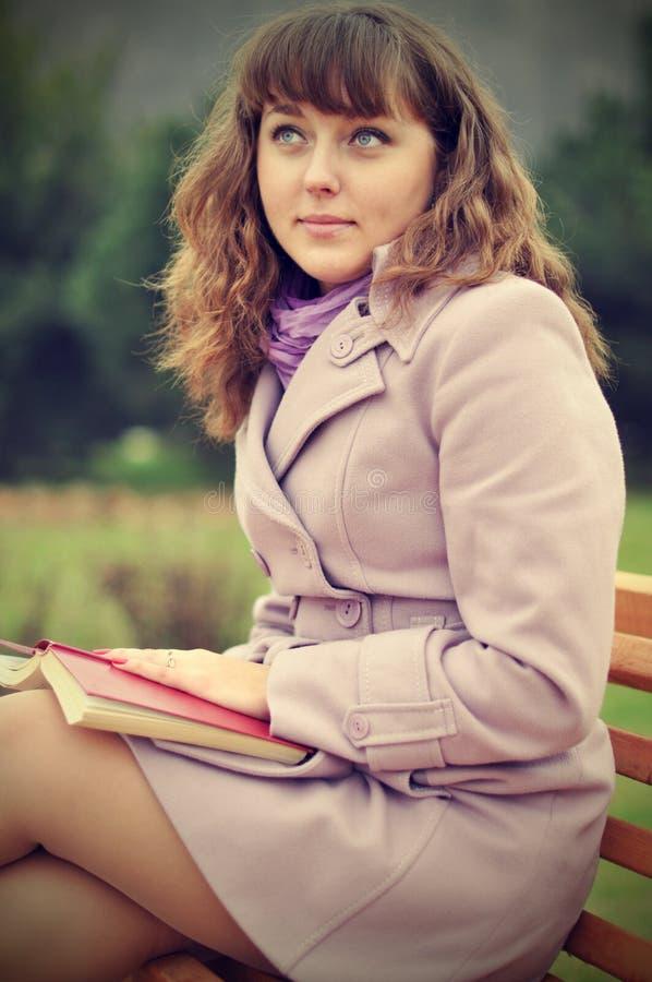 Les femmes lit un livre en parc image stock