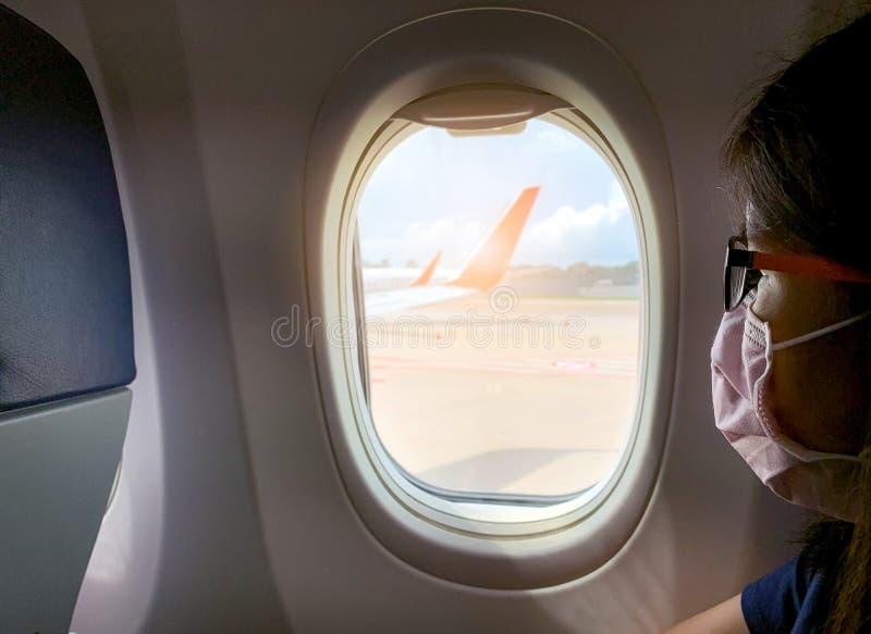 Les femmes malades portant un masque et des lunettes sont assis sur le siège de l'économie de passagers près de la fenêtre de cab images libres de droits