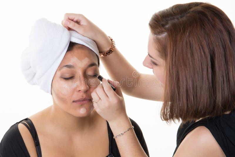 les femmes préparent l'artiste appliquant le mascara pour modeler la fille images libres de droits