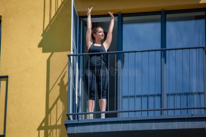 Les femmes pratiquent le sport sur le balcon de l'appartement images libres de droits