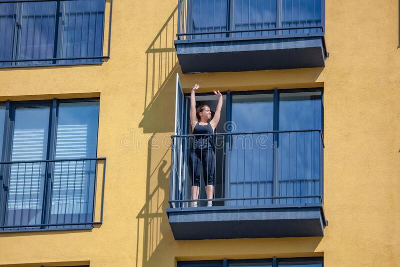 Les femmes pratiquent le sport sur le balcon de l'appartement photos libres de droits