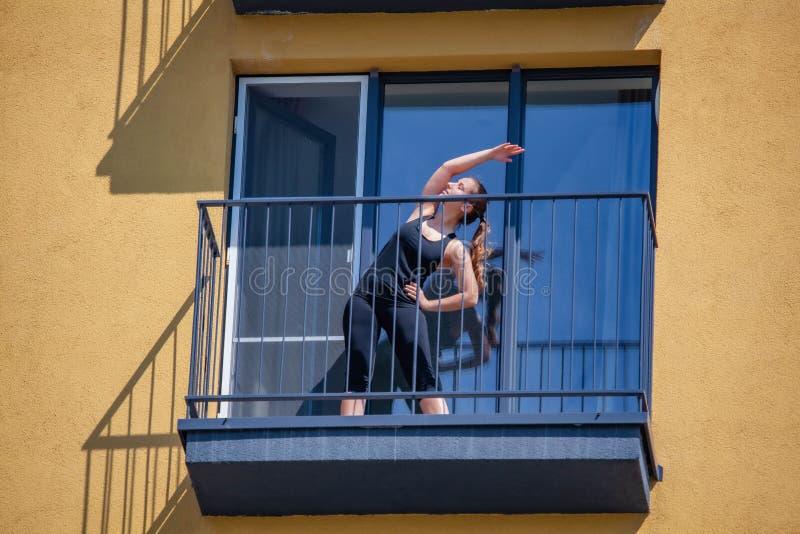 Les femmes pratiquent le sport sur le balcon de l'appartement photographie stock