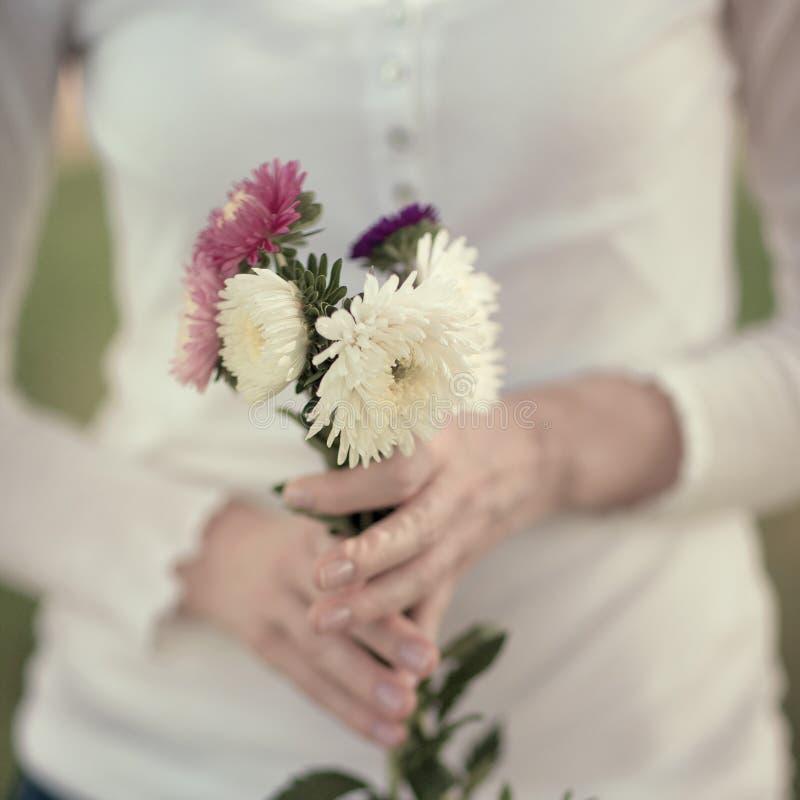 Les femmes remet tenir des fleurs dans un domaine rural dehors, convoitise pendant la vie photos libres de droits
