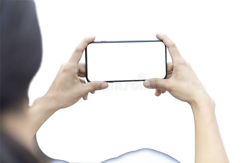Les femmes remettent tenir le smartphone horizontal avec l'écran vide pour prendre une photo D'isolement sur le fond blanc ?conom photographie stock
