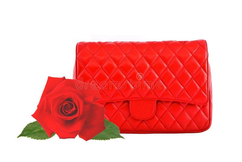 Les femmes rouges mettent en sac et la rose de rouge d'isolement sur le blanc image stock