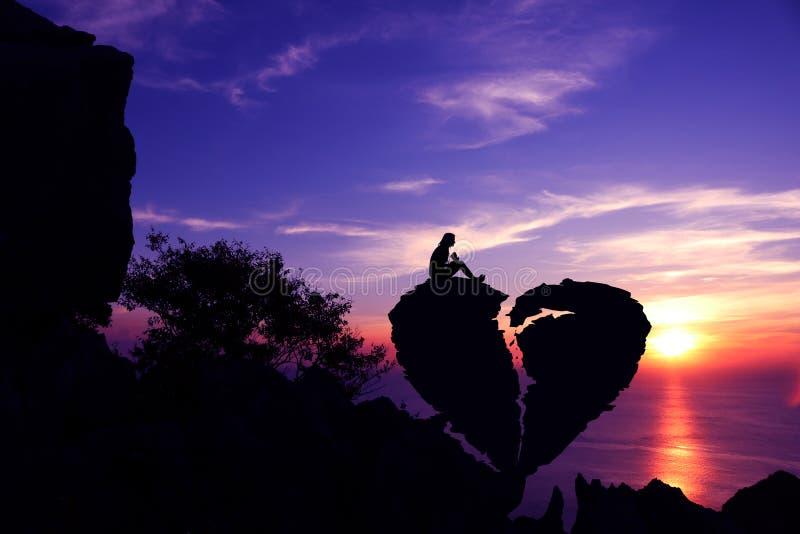 Les femmes s'asseyent sur la pierre en forme de coeur cassée sur une montagne photos libres de droits
