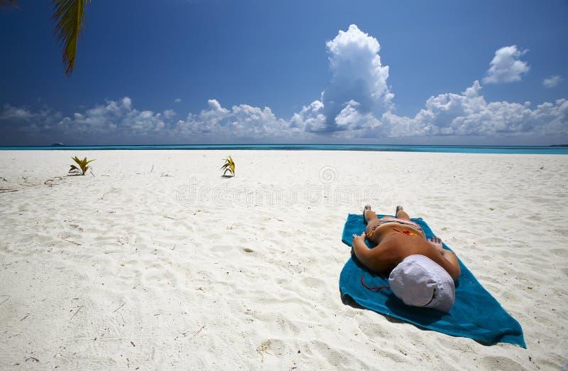 Les femmes se décolore au soleil sur la plage sablonneuse photo stock