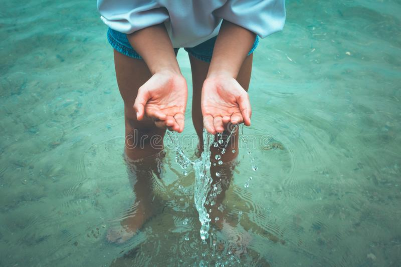 Les femmes se tiennent dans l'eau et les mains cherchent l'eau et avoir l'éclaboussure de l'eau image stock