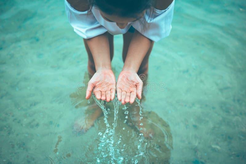 Les femmes se tiennent dans l'eau et les mains cherchent l'eau et avoir l'éclaboussure de l'eau photographie stock