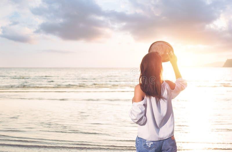 Les femmes se tiennent sur la plage et l'eau de mer entre le coucher du soleil et le nuage gentil photo stock