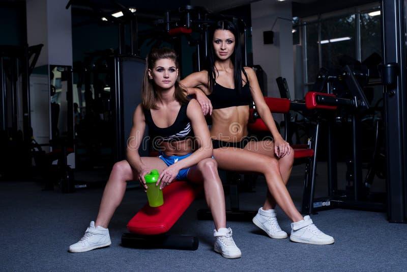 Les femmes sexy de forme physique dans les vêtements de sport se reposant après des haltères s'exerce dans le gymnase Belles fill images libres de droits
