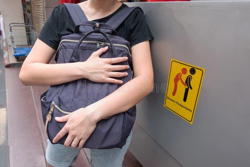Les femmes sont pickpocket soigneux parce qu'elle voient prennent garde des pickpockets signent le symbole photos stock