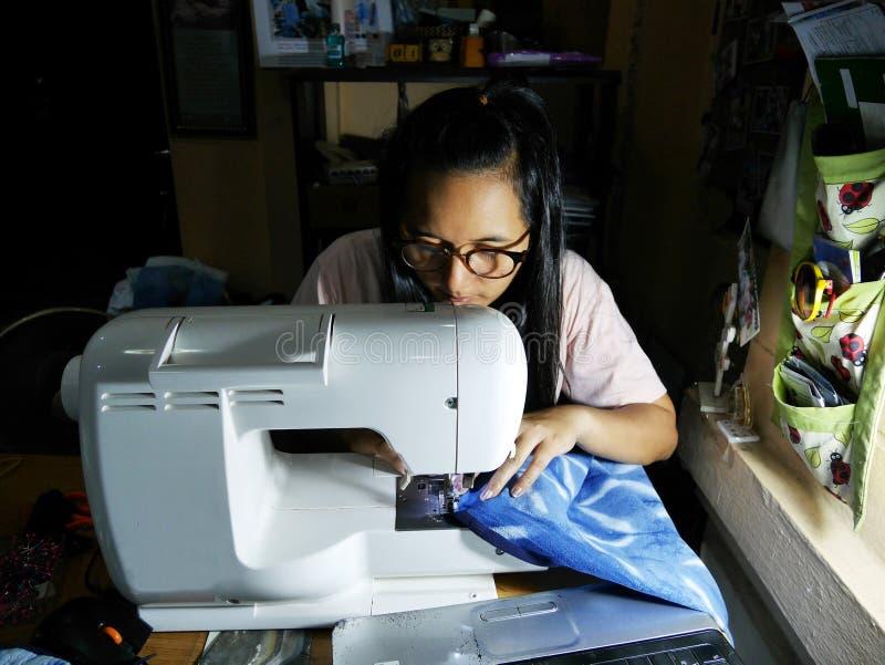 Les femmes thaïlandaises asiatiques utilisent la machine cousant et la mode créative de vêtements de conception dans l'atelier de photographie stock