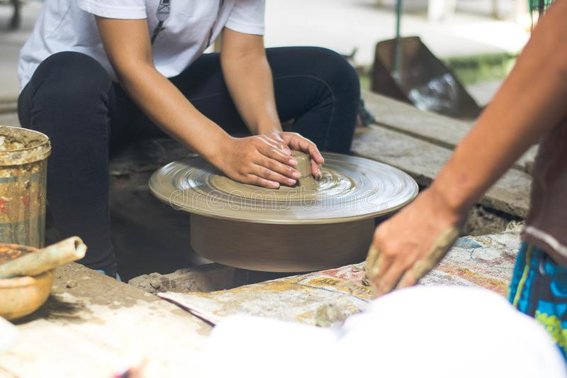 Les femmes thaïlandaises employant la pratique en matière de poterie de mécanicien sculptent la poterie de terre photos stock