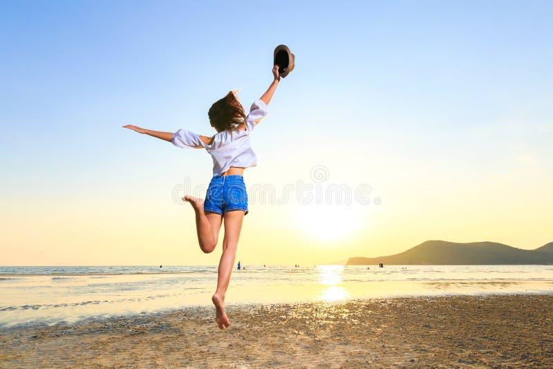 Les femmes tiennent et tiennent le chapeau sur la plage entre le coucher du soleil photos stock