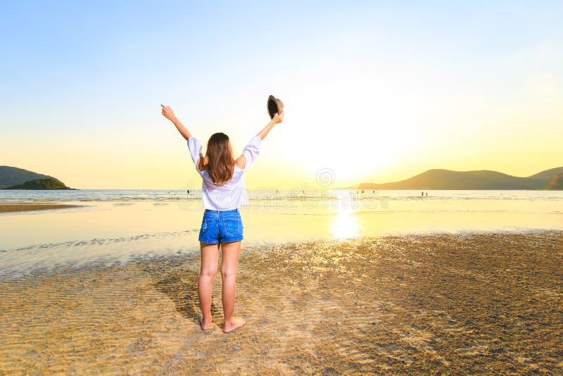 Les femmes tiennent et tiennent le chapeau sur la plage entre le coucher du soleil photo libre de droits