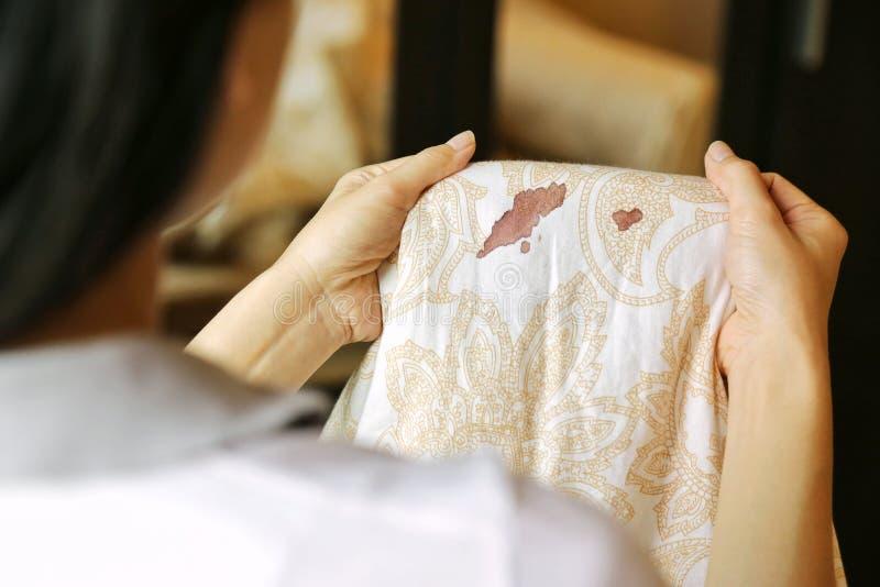 Les femmes tiennent le drap avec des taches de tache de sang de période sur le fond de tache floue Le besoin de nettoyer images stock