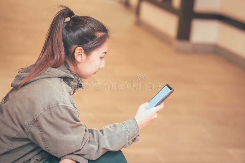 Les femmes tiennent le téléphone portable pour le message et l'email de contrôle photo libre de droits
