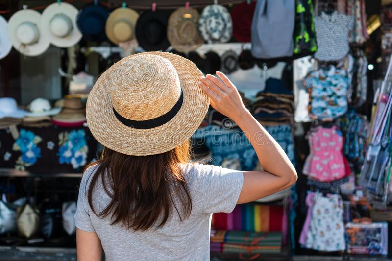 Les femmes tiennent un chapeau et regarder la boutique de souvenirs photographie stock
