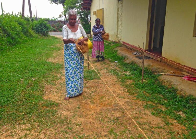Les femmes tissent la corde du coprah de noix de coco images libres de droits