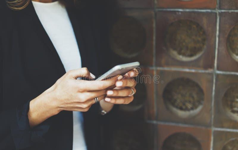 Les femmes utilisant le smartphone d'isolement, directeur de hippie tenant l'instrument mobile, sms de message textuel de fille,  photos libres de droits
