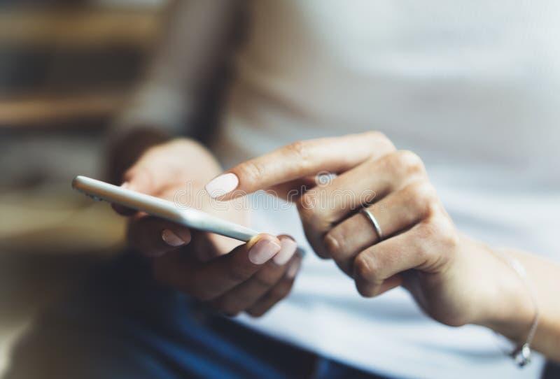 Les femmes utilisant le smartphone, directeur de hippie tenant l'instrument mobile, sms de message textuel de fille, relient le c photo stock