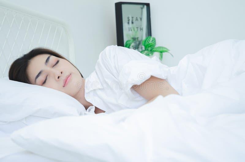Les femmes utilisant les pyjamas blancs se reposent photographie stock