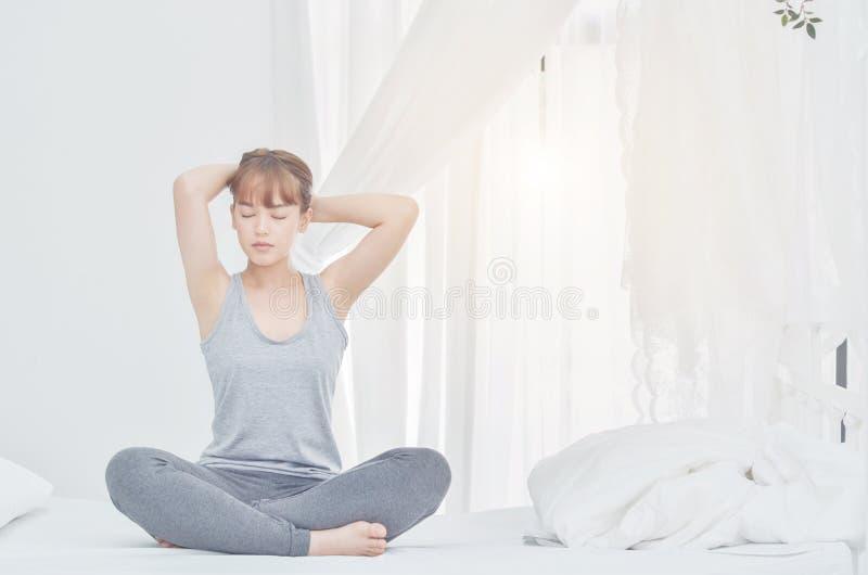 Les femmes utilisant les pyjamas gris se reposant sur le divan utilisent la poignée au pied photo stock