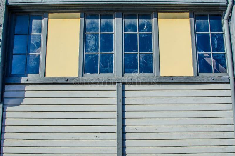 Les fenêtres jumelles sur la vieille maison de bois de construction image stock