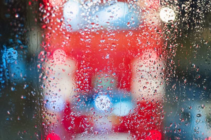 Les fenêtres rouges d'autobus à impériale d'autobus de Londres pleuvoir la nuit de réverbères de tache floue photo libre de droits