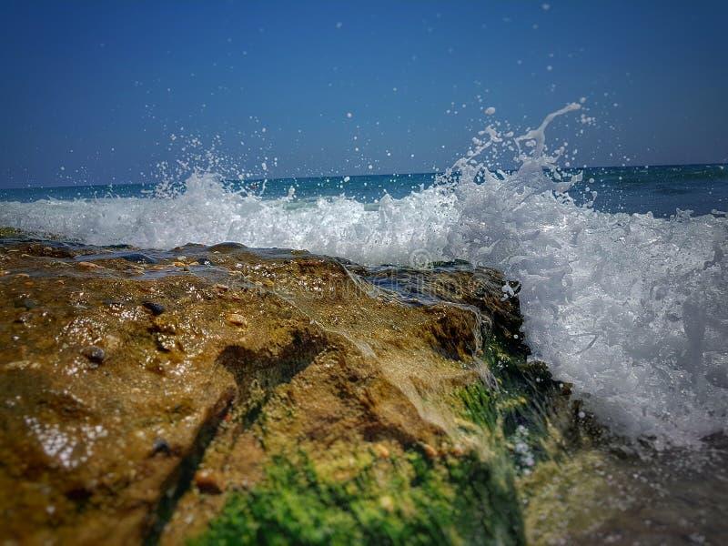 les fentes ondule contre des roches en mer La mer Méditerranée ondule se briser sur les roches Pierre en mer avec la vague le tem photo stock