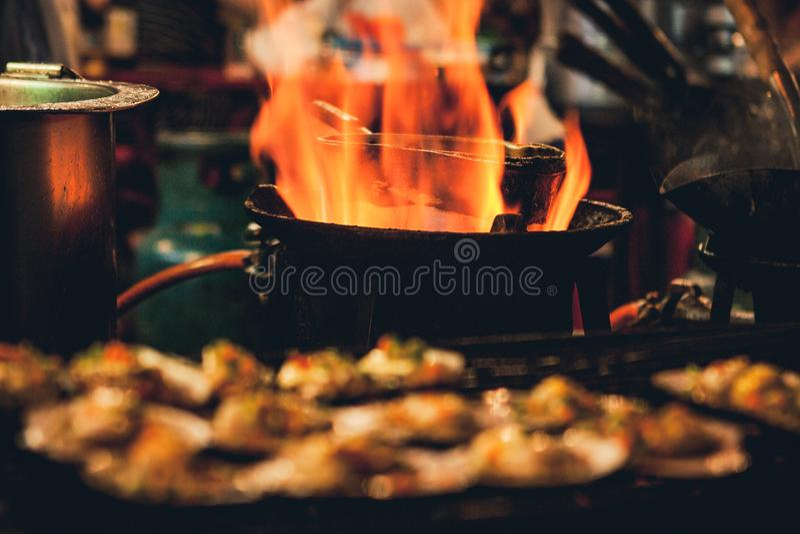 Les festons grillés vendus à un marché en plein air calent avec une casserole couverte de flammes sur le fond Chinatown, Bangkok, images libres de droits