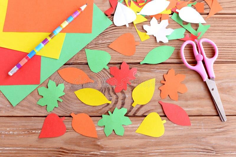 Les feuilles colorées d'automne ont coupé du papier, crayon, les ciseaux, feuilles de papier coloré sur un fond en bois Coupe de  photos libres de droits