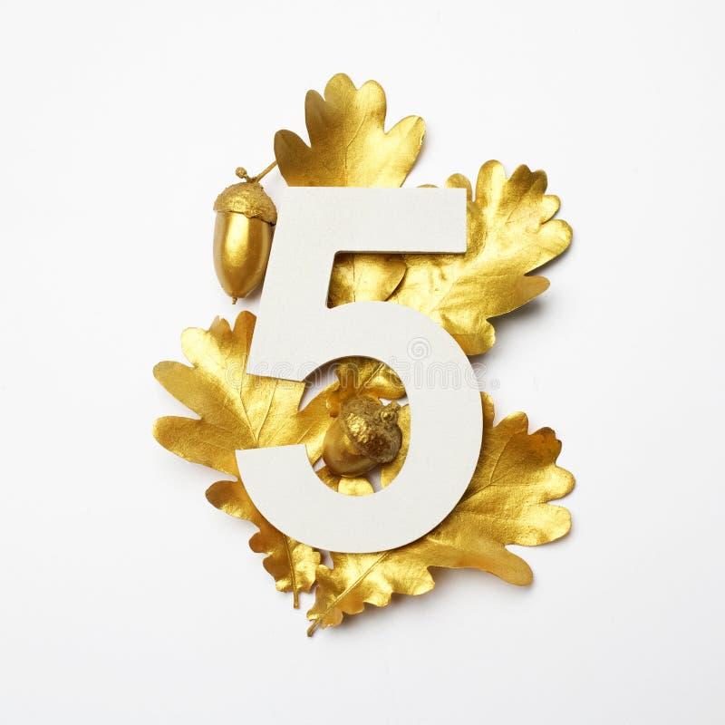 Les feuilles d'or de chêne et numéro cinq sur le fond gris-clair image libre de droits