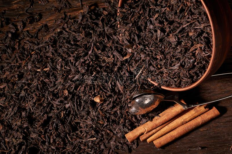 Les feuilles de thé sèches en argile roulent sur le fond noir Foyer sélectif photographie stock libre de droits