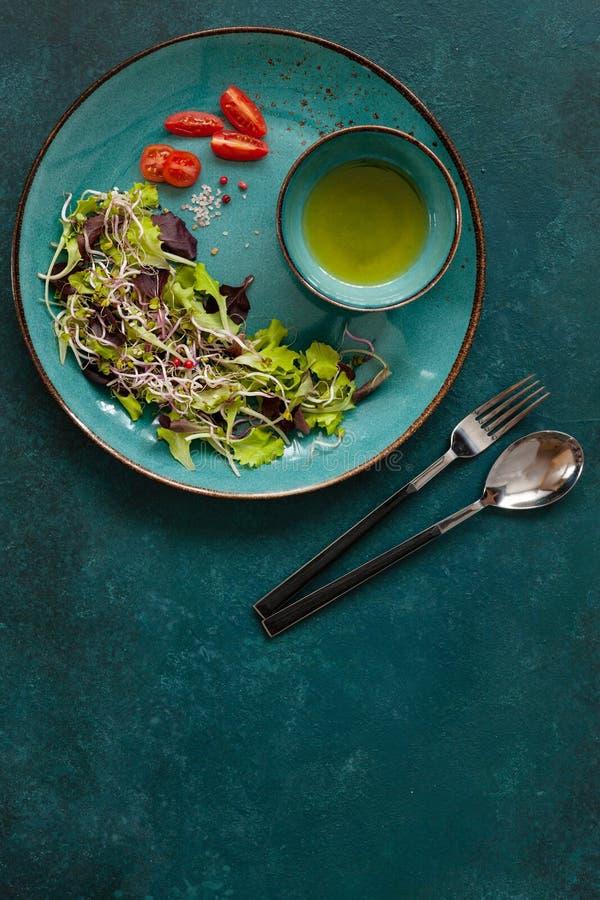 Les feuilles mélangées fraîches de salade de bébé, porcelaine organique se sont levées des pousses avec l'huile d'olive sur le fo photo stock