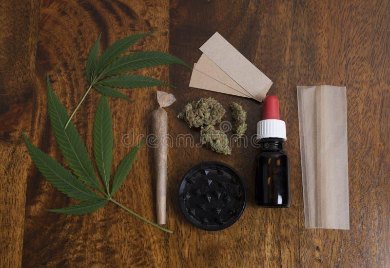 Les feuilles sativa de cannabis et les THC huilent, avec la broyeur et les papiers pour fumer le joint de mauvaise herbe image libre de droits