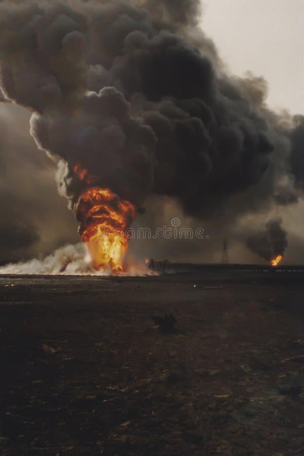 Les feux brûlants de puits de pétrole dans le domaine avec marée de noir, Kowéit photographie stock libre de droits