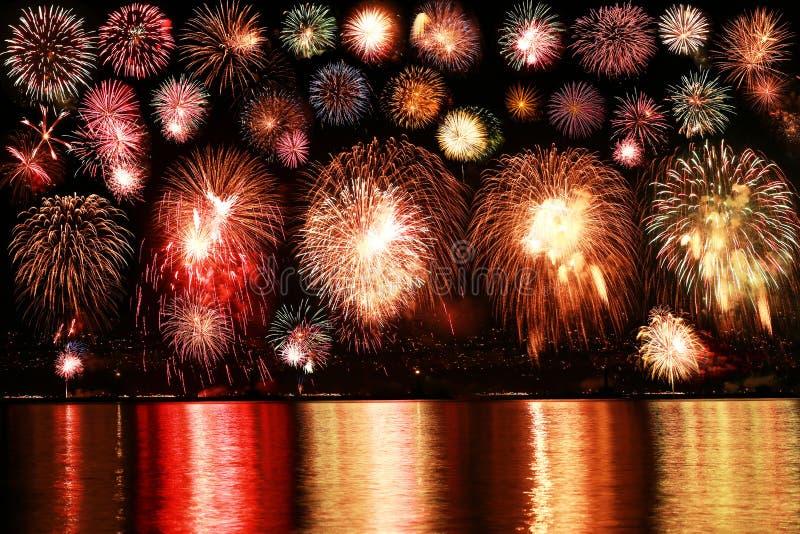 Les feux d'artifice colorés se reflètent de l'eau image libre de droits