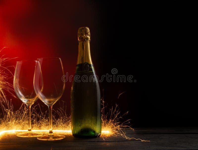 Les feux d'artifice ont blâmé admirablement sur deux verres de vin vides et une bouteille de vin image stock