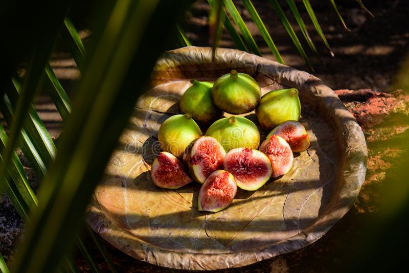Les figues mûres d'un plat des feuilles se ferment  Fruits tropicaux frais : figues coupées en tranches douces images libres de droits