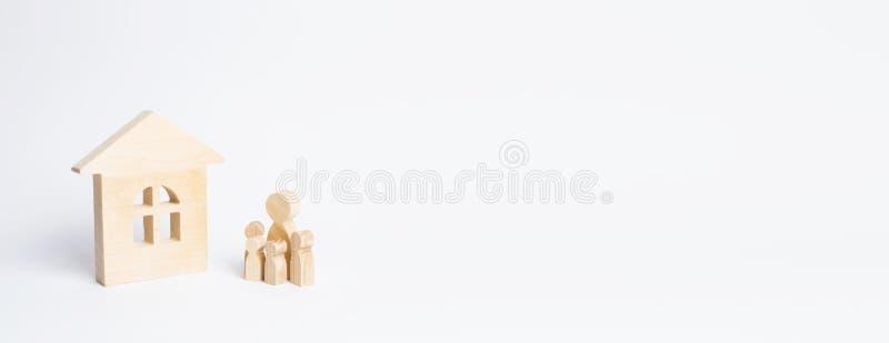Les figures des personnes avec des enfants se tiennent près d'une maison en bois sur un fond blanc Le concept des immobiliers et  photo stock