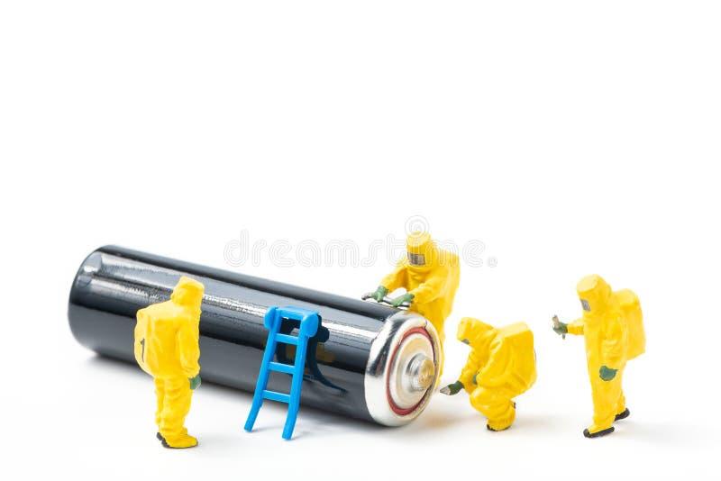Les figurines dans la tenue de protection examinent une batterie utilisée photos stock