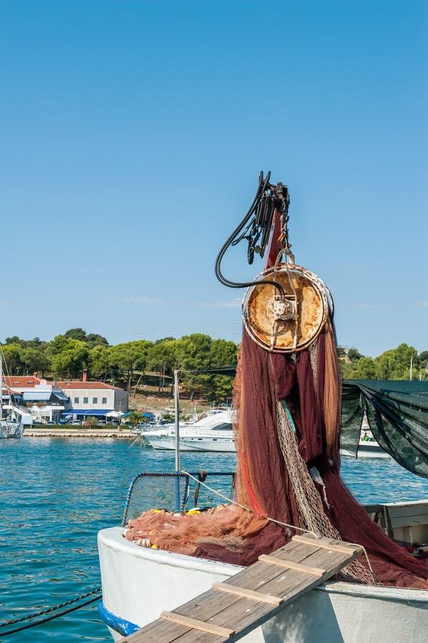 Les filets de pêche soulève la grue sur la jetée par la mer Produits des pêches Réparation des réseaux photo stock