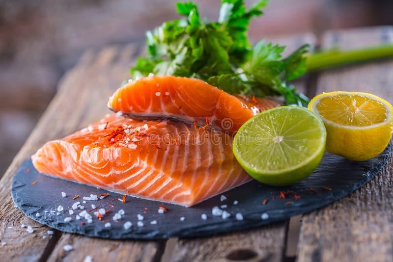 Les filets saumonés crus avec des herbes de persil chaulent le sel de citron et ont séché photos libres de droits