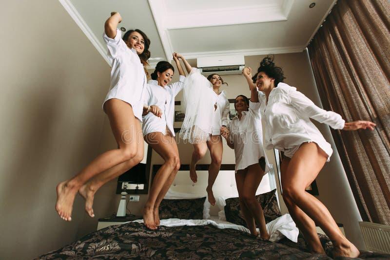 Les filles émotives avec une jeune mariée sautent sur le lit photographie stock libre de droits