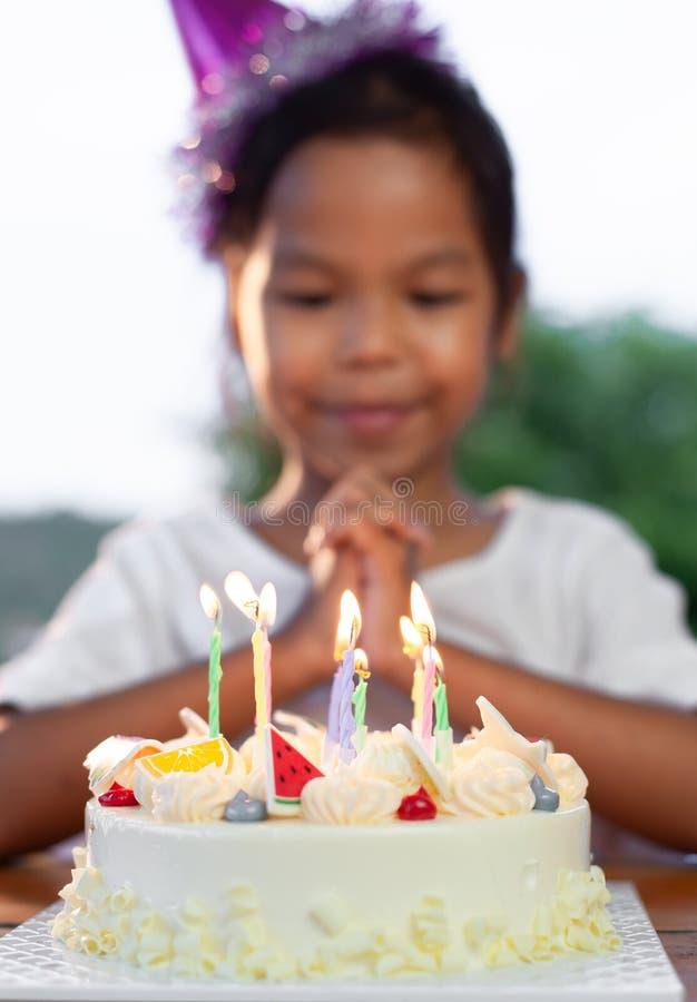 Les filles asiatiques d'enfant font la main pliée pour souhaiter les bonnes choses son anniversaire en fête d'anniversaire photographie stock