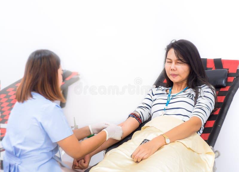 Les filles asiatiques ont effrayé l'aiguille et pleurer de sang Procédure de transfusion sanguine images stock